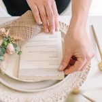 setting the table with a multi colored menu in earth tones and deckled edging wedding planning event design