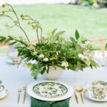 A fresh greenery centerpiece decorates a tablescape set with modern and vintage decor.