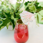 A bright red specialty cocktail with a decorative paper umbrella sits in front of fresh greenery.