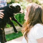 A guest nuzzles up to a goat at a baby shower petting zoo.