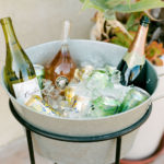 A decorative galvanized ice bucket holds wine, champagne and La Croix for a backyard baby shower.