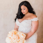 A bride poses with her tree peony bouquet in a textured Della Curva dress