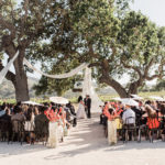 A bride and groom stand at the ceremony overlooking the vines at Sunstone Winery.