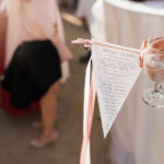 A ceremony program is fashioned into a pennant with a bell and ribbon streamers