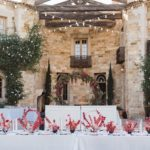 a dinner table is decorated with crisp white linen and bright modern pink and red flower centerpieces.