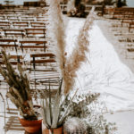 Potted cactus, eucalyptus and pampas grass cap the aisle at this late summer boho wedding ceremony at Torrey Pines Reserve in La Jolla, CA.