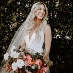 A beautiful blushing bride holds her colorful boho bouquet and wears a detailed Untamed Petals cap veil.