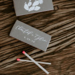 Custom matchboxes with hot pink matches are decorated with the bride and groom's names, wedding date and cactus detail.