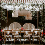 The bride and groom's dinner table has special peacock chairs and bougainvillea accents for their late summer wedding at Inn at Rancho Santa Fe.