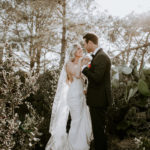 A bride and groom pose amongst the foliage at Torrey Pines Reserve, the location of their late summer wedding ceremony.