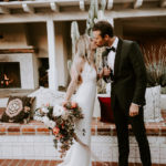 A boho bride and groom toast and kiss at their late summer wedding at Inn at Rancho Santa Fe.