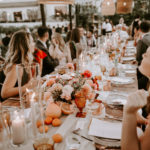 Guests are seated at feasting tables decorated with colorful centerpieces of floral, fruit and candles under a canopy of draped fabric and boho wicker lanterns at this late summer wedding at Inn at Rancho Santa Fe.