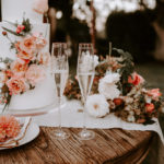 Toasting flutes sit next to a beautiful white tiered wedding cake with fresh floral detail on a boho table at this late summer wedding at Inn at Rancho Santa Fe.
