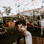 A surprise confetti canon goes off during the bride and groom's first dance at this late summer wedding at Inn at Rancho Santa Fe.